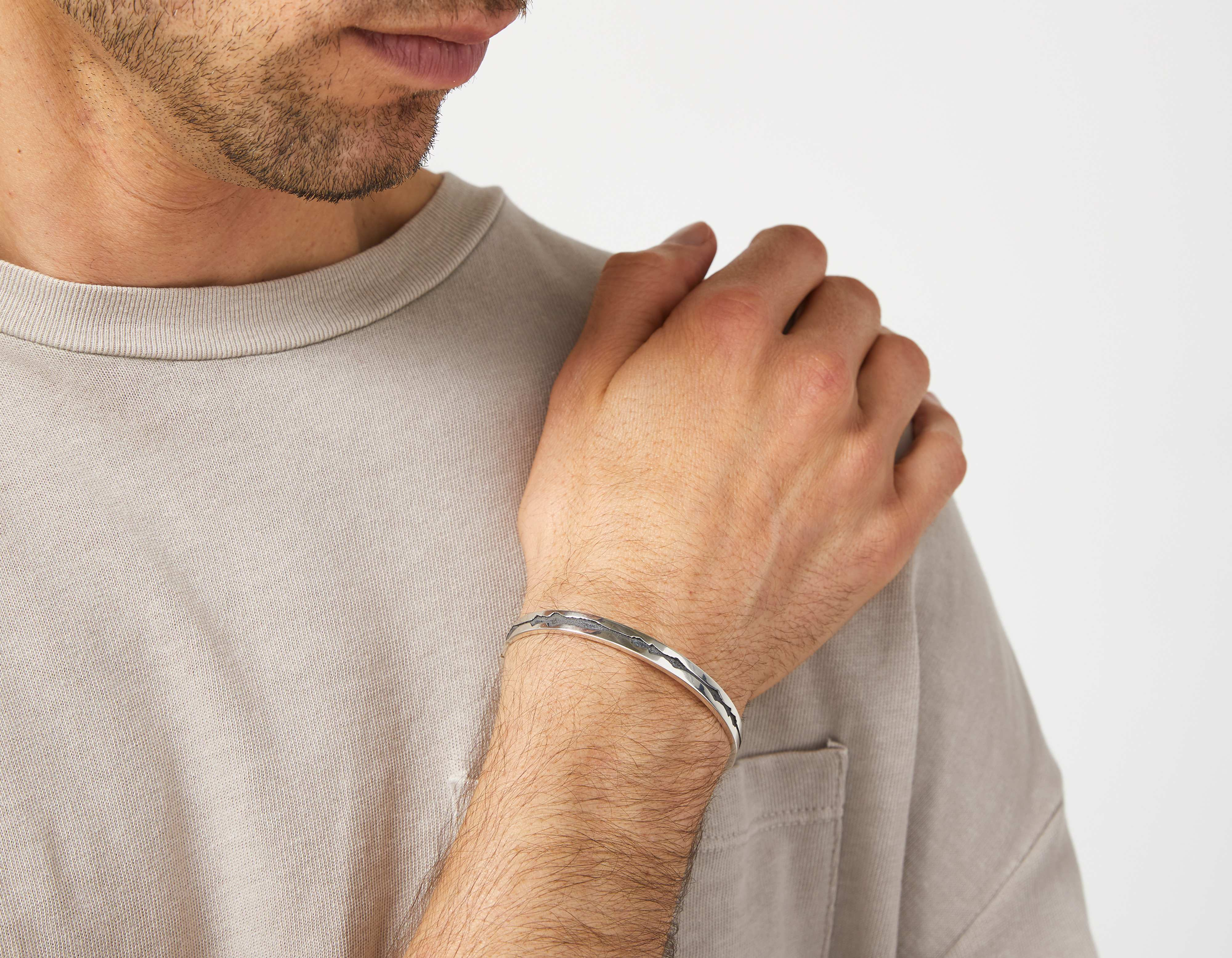 The Outer Wave Bracelet in Antiqued Sterling Silver on a male